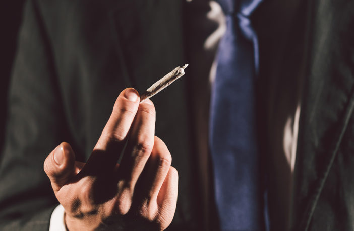 Cannabis policy in the workplace. A man in a suit holds a joint.