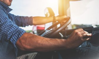 A truck driver shifts gears with one hand on the steering wheel.