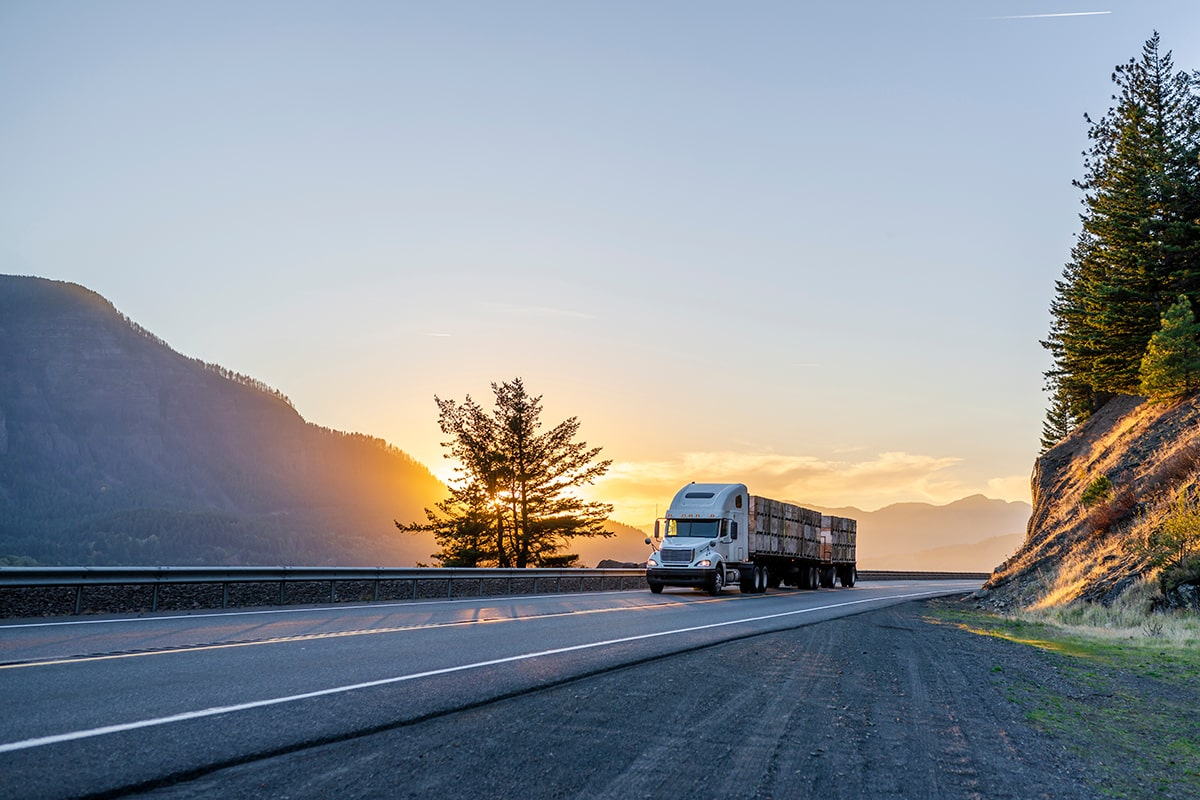 A semi truck drives on a road with the sunsetting in the background.