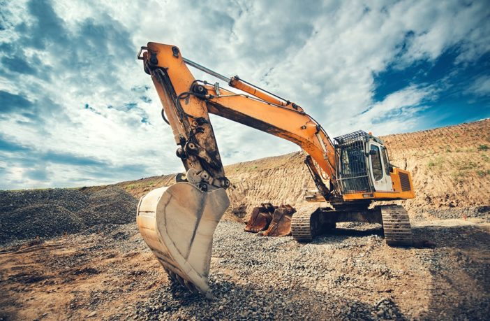 An excavator digs into the ground with a blue sky as the background.