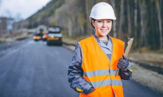 A female road workers in a hard hat and safety vest smiles while holding a clipboard
