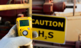 An oilfield worker holds an H2S monitor next to an H2S warning sign.
