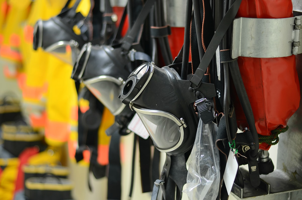 A row of SCBA breathing apparatus hung up on a wall.