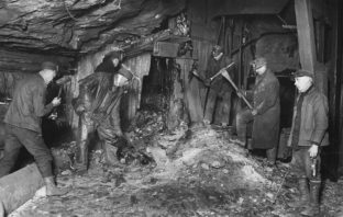 A black and white photo of a group of miners in a mine shaft.