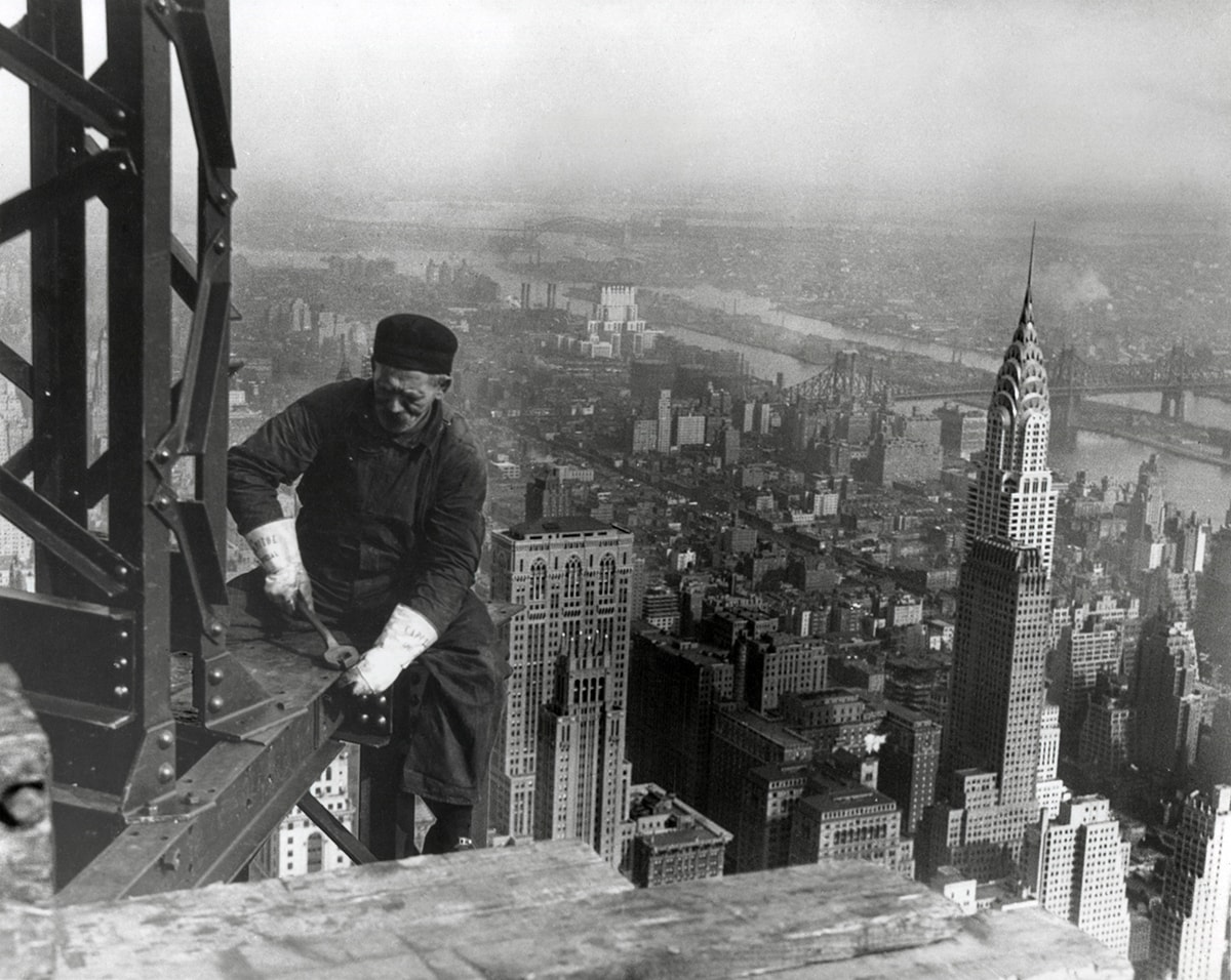 A black and white photo of an iron worker with the Empire State Building in the background.