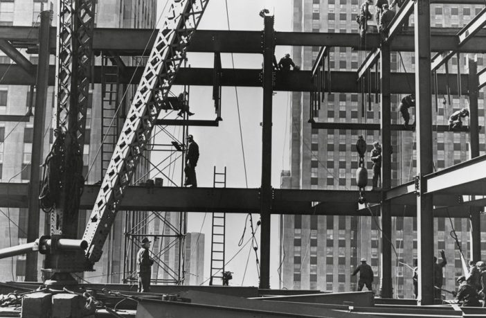 A black and white photograph of construction workers working at heights with no fall arrest protection.